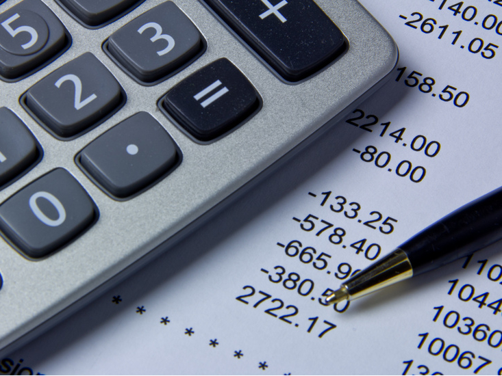 Calculator, pen and paper with budget numbers used to determine school fundraising goals