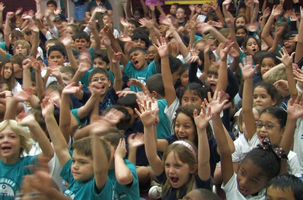 Audience of students at a big event school fundraising prize assembly