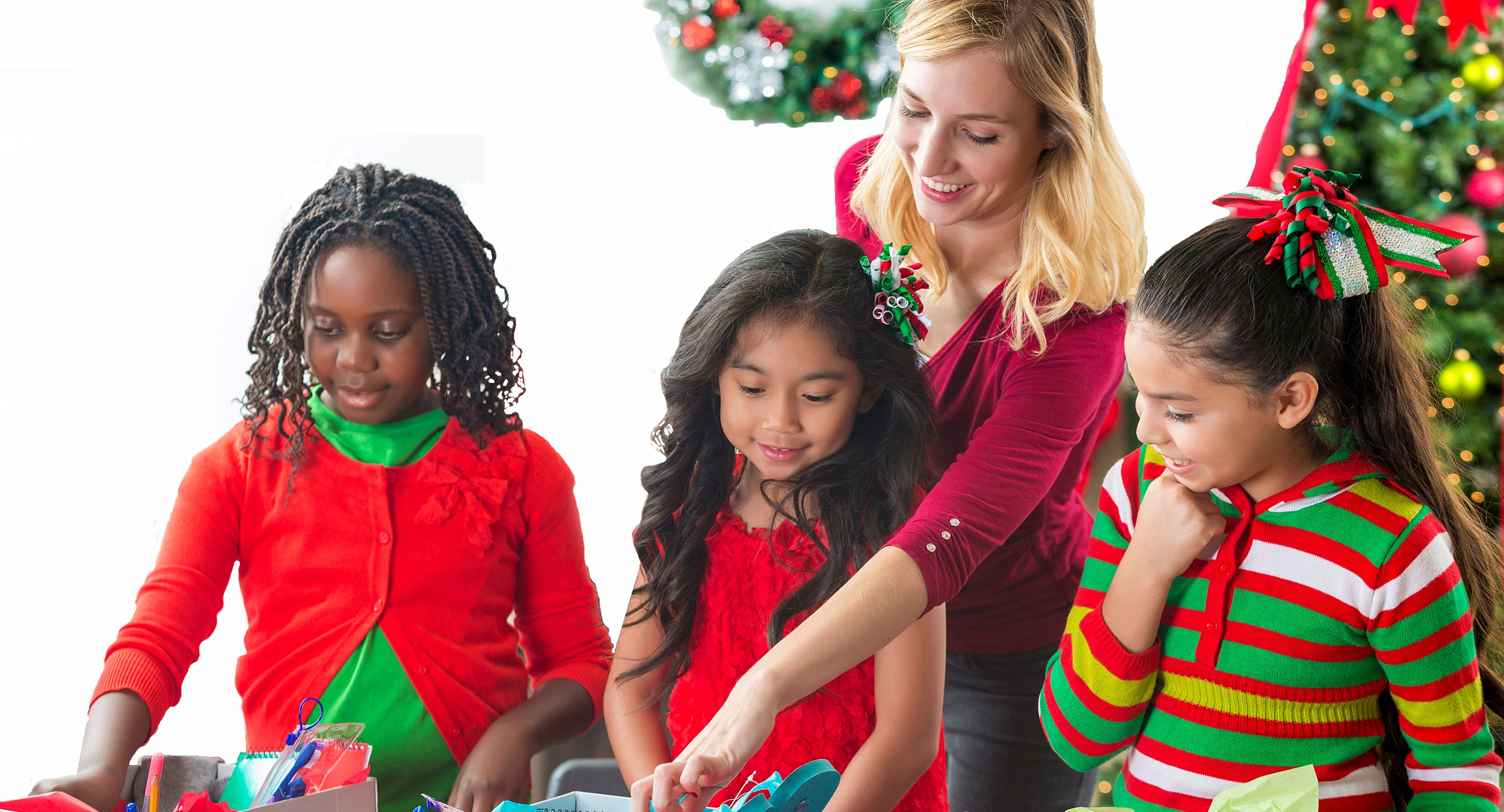 Woman with girls wrapping presents in front of a Christmas tree