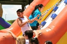 Students on water slide at super splash party event